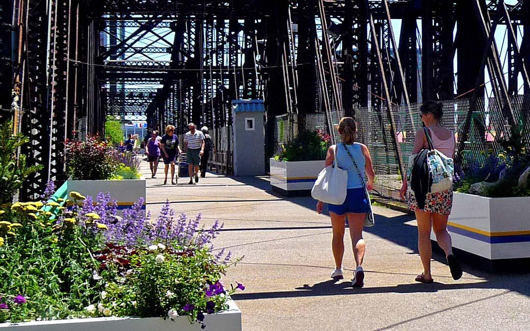 Northern avenue bridge-ladies with bags walking-couple in distance walking towards-bottomr ight corner flowers