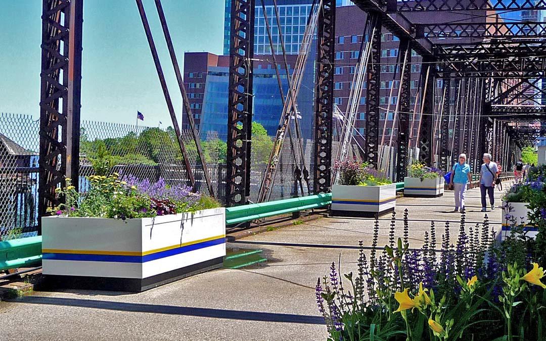 Northern avenue bridge-plants on left focus-elderly couple walking